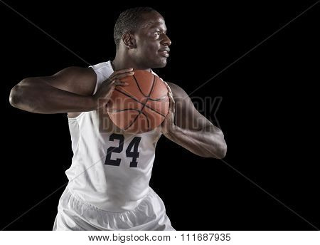 African American Basketball Player playing basketball. Shot on a dark background