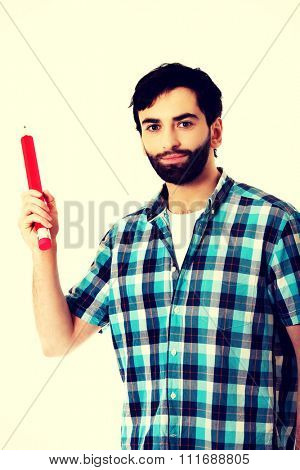 Young man pointing with oversized red pencil.
