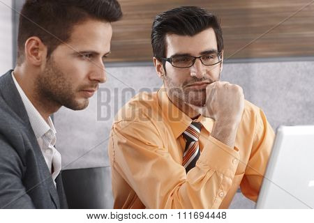 Businessmen working with laptop computer, concentrating.