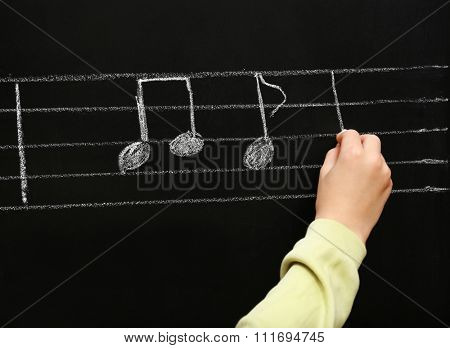 View on boy's hand writing at the blackboard with musical notes, close-up