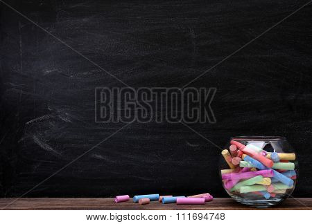 Multicoloured chalk in aquarium on blackboard background