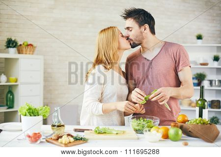 Affectionate young couple kissing while cooking salad