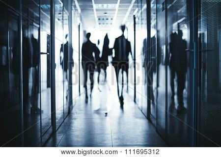 Blurred silhouettes of business people moving in aisle between offices