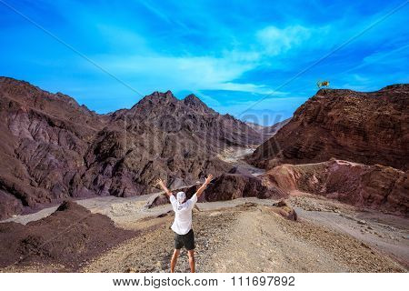 Lone tourist threw his hands up in delight in Eilat Mountains. Unique  outcrops  in the mountains of pink sandstone