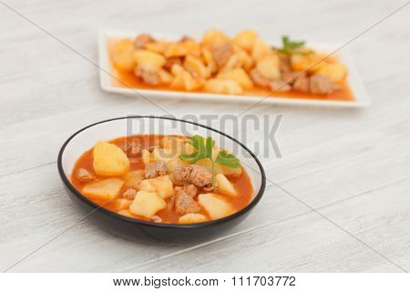 Hearty beef stew simmering on gray wooden background