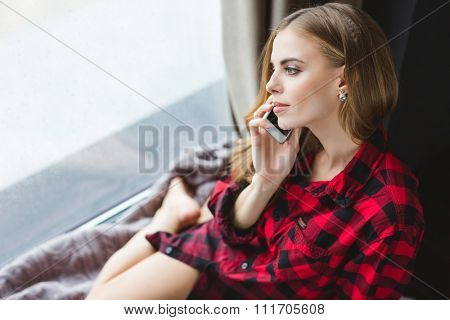 Attractive sensual girl in plaid shirt talking on mobile phone and looking out of the window