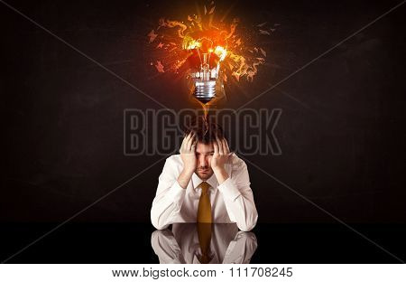Depressed businessman sitting under a blowing idea bulb