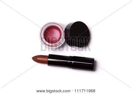 Golden red lipstick and lip gloss in jar, top view isolated on white background
