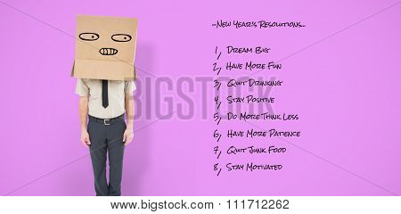 Businessman standing with box on head against pink