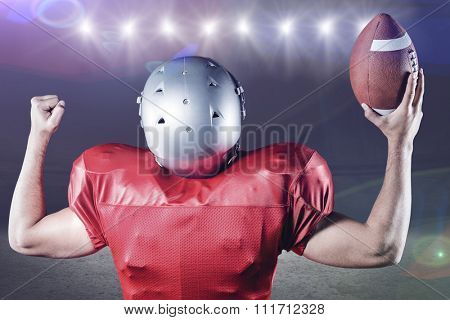 Rear view of American football player cheering while holding ball against desert landscape