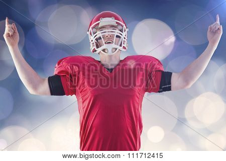 American football player triumphing against glowing christmas background