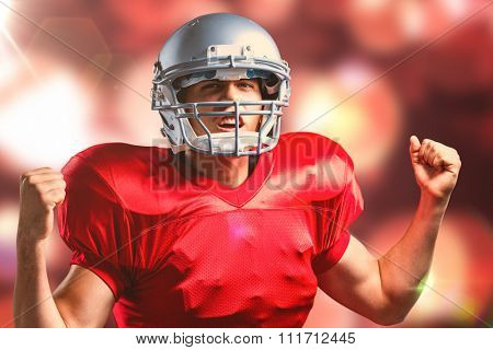Portrait of American football player cheering with clenched fist against twinkling red and orange lights