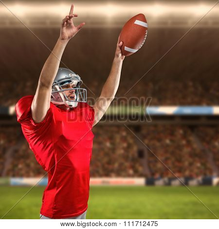 American football player holding ball while pointing up against rugby fans in arena