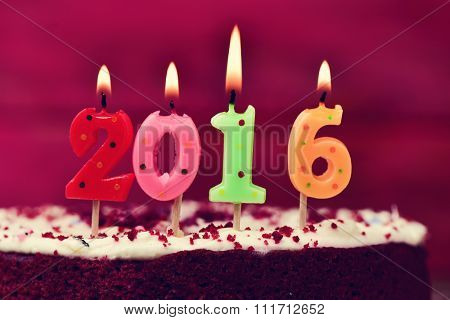 closeup four lit number-shaped candles of different colors forming the number 2016, as the new year, on a cake