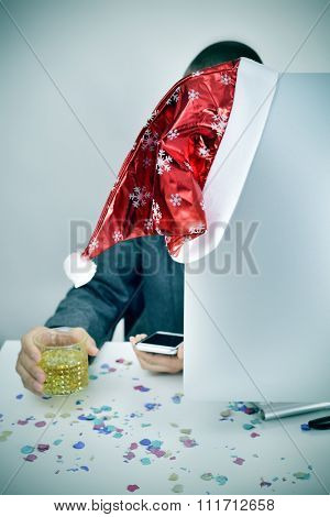 a young caucasian businessman with a glass of liquor in one hand and a smartphone in the other, sitting at his office desk covered with confetti and a santa hat