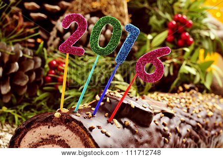 a yule log cake, traditional of christmas time, topped with glittering numbers of different colors forming the number 2016, as the new year