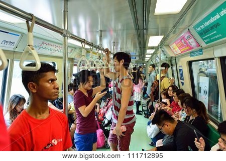 SINGAPORE - NOVEMBER 07, 2015: passengers in MRT train. The Mass Rapid Transit, or MRT, is a rapid transit system forming the major component of the railway system in Singapore.
