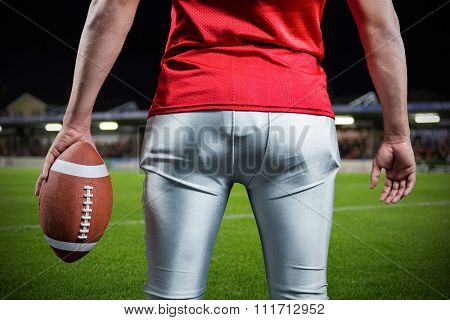 Mid section of sportsman with American football against pitch and stands