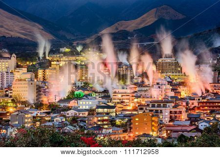 Beppu, Japan cityscape with hot spring bath houses and rising steam.