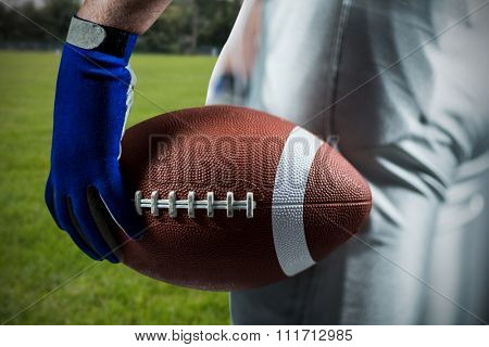 Cropped image of sportsman holding American football ball ball against rugby ball on the pitch
