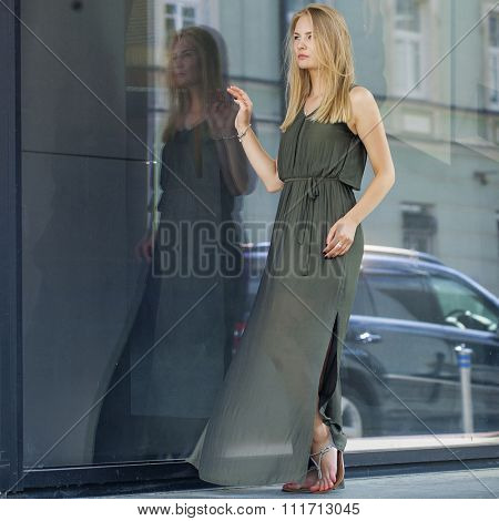 Portrait in full growth, Young beautiful blonde woman in long green dress posing against a background of a wall mirror