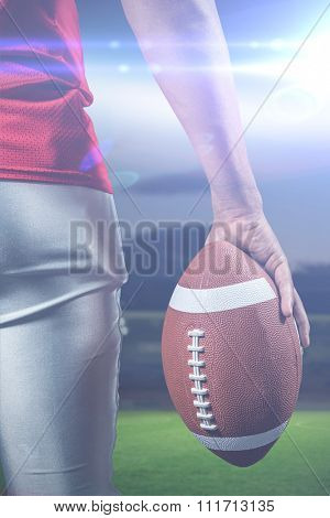 Cropped image of American football player holding ball against rugby pitch