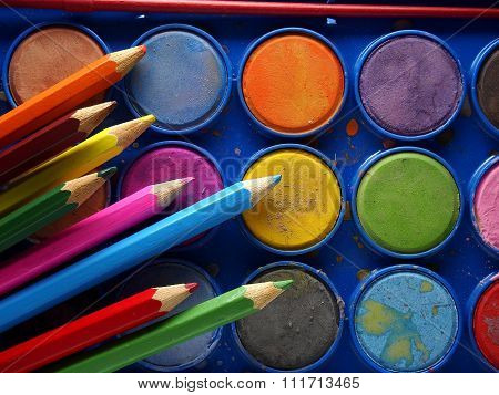 Pallette of water colors and colored pencils