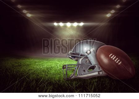 American football helmet and ball against rugby stadium