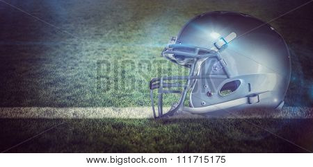 American football helmet against rugby pitch