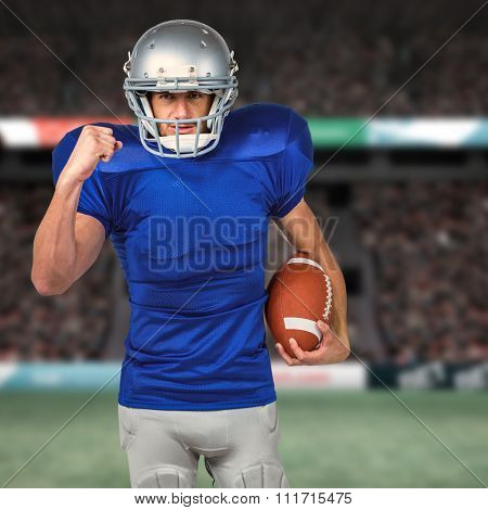 Portrait of American football player running with ball against rugby fans in arena