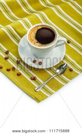 White porcelain cup with coffee on napkin. Isolated on white background