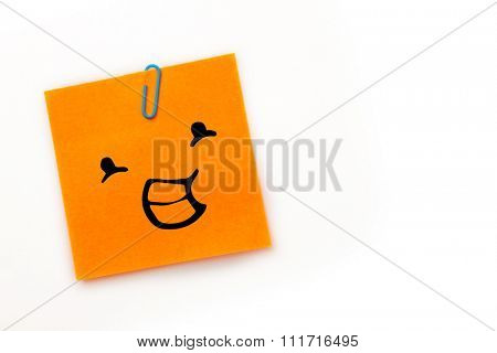 Smiling face against orange adhesive note with a paperclip