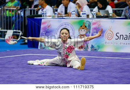 JAKARTA, INDONESIA - NOVEMBER 17, 2015: Emily Fan of the USA performs the movements in the women's Jianshu event at the 13th World Wushu Championship 2015 in Istora Senayan Stadium.
