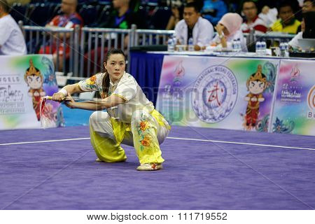 JAKARTA, INDONESIA - NOVEMBER 17, 2015: Stephanie Lim of the USA performs the movements in the women's Gunshu event at the 13th World Wushu Championship 2015 in Istora Senayan Stadium.