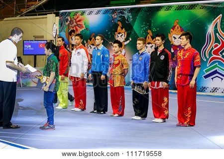 JAKARTA, INDONESIA - NOVEMBER 17, 2015: Athletes taking part in the men's Compulsory Changquan event parade for the judges at the 13th World Wushu Championship 2015 in Istora Senayan Stadium.