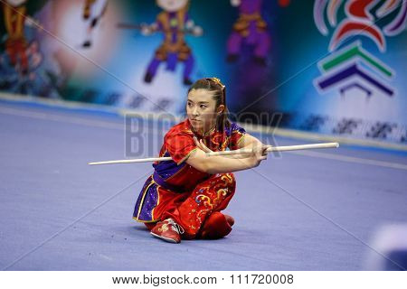 JAKARTA, INDONESIA - NOVEMBER 17, 2015: Fong Wei Chai of Malaysia performs the movements in the women's Gunshu event at the 13th World Wushu Championship 2015 in Istora Senayan Stadium.