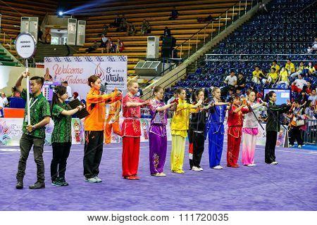 JAKARTA, INDONESIA - NOVEMBER 17, 2015: Athletes taking part in the women's Jianshu event parade for the judges at the 13th World Wushu Championship 2015 in Istora Senayan Stadium.