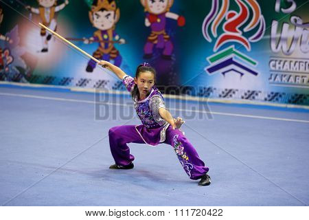 JAKARTA, INDONESIA - NOVEMBER 17, 2015: Lucy Ruxi Lee of the USA performs movements in the Women's Nangun event at the 13th World Wushu Championship 2015 in Istora Senayan Stadium.