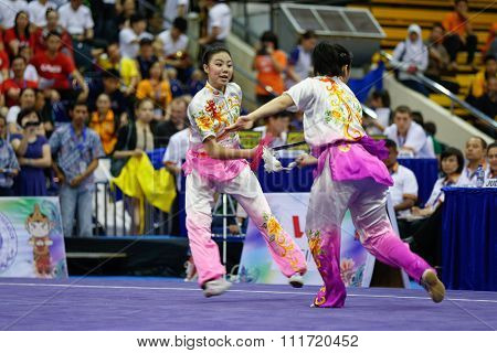 JAKARTA, INDONESIA - NOVEMBER 17, 2015: The USA women's duel team performs the action fights in the Women's Duel event at the 13th World Wushu Championship 2015 in Istora Senayan Stadium.