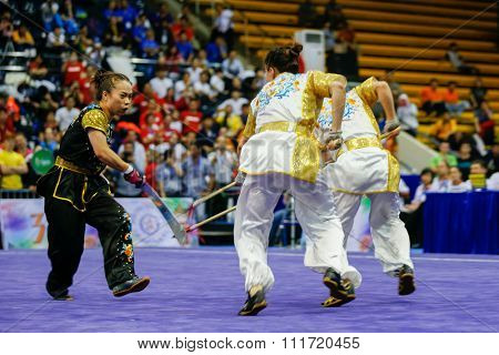 JAKARTA, INDONESIA - NOVEMBER 17, 2015: The Hong Kong women's duel team performs the action fights in the Women's Duel event at the 13th World Wushu Championship 2015 in Istora Senayan Stadium.