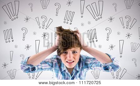 Pretty brunette getting a headache with hands on head against grey background