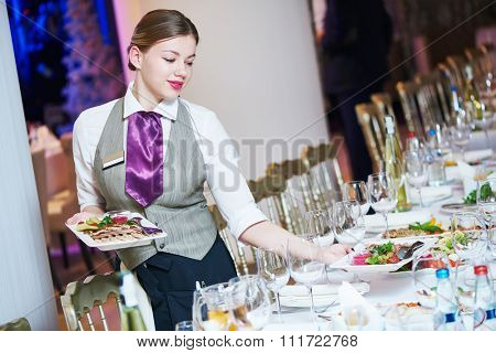 Restaurant catering services. Waitress with food dish serving banquet table