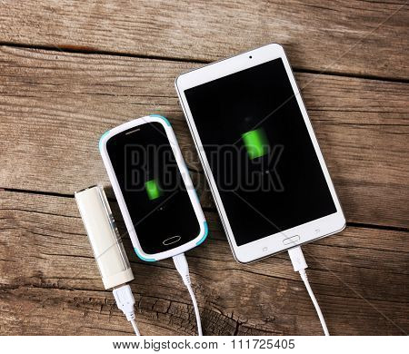 a phone and a tablet being charged with a power hub bank toned with a retro vintage instagram filter app or action effect