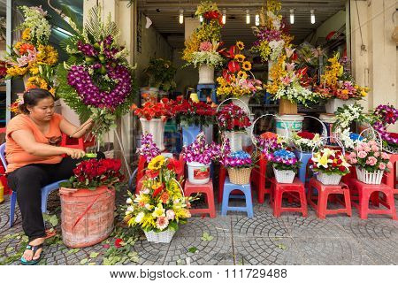 HO CHI MINH VILLE, VIETNAM, FEBRUARY 24, 2015 : Woman preparing flower composition for selling during the Chinese new year, called Tet, at the Ben Thanh market in Ho Chi MInh (Saigon), Vietnam