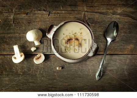 Mushroom soup  with spoon and fresh vegetables on a rustic background