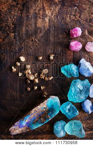 Treasure hunting. Mining for gems. Gold and gem stones on rough wooden surface.