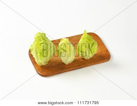 hearts of fresh romaine lettuce on wooden cutting board