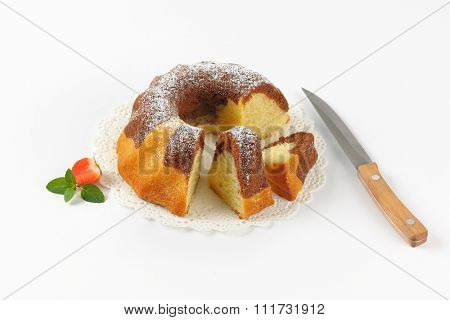 sliced marble bundt cake on white lace and kitchen knife