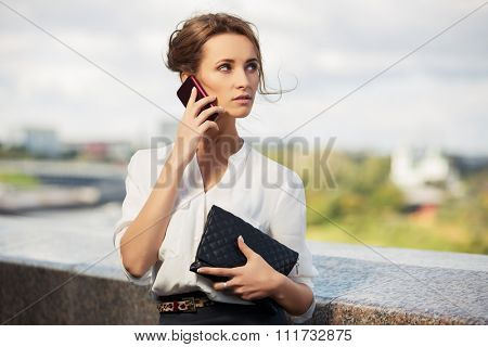 Young fashion business woman with handbag calling on mobile phone outdoor