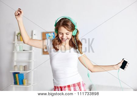 people, leisure and technology concept - happy woman or teenage girl in headphones listening to music from smartphone and dancing on bed at home